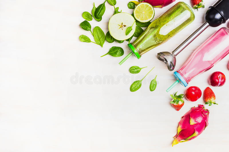 Green and red Smoothie bottles with fresh ingredients and electric blender on white wooden background, top view, border. royalty free stock photos