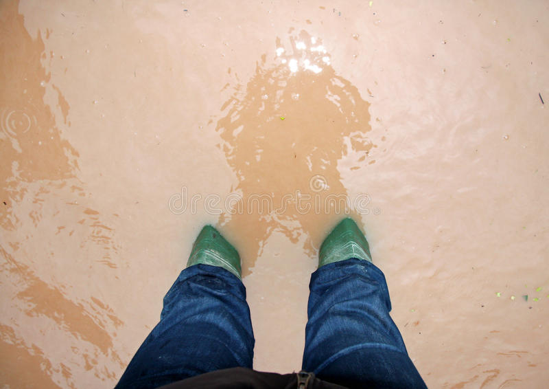 Green rescuer boots during a flood in the city royalty free stock photography