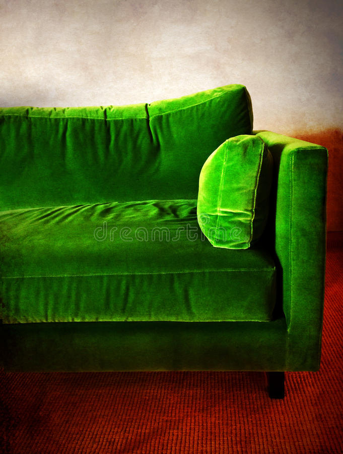 Green retro sofa in a room. Green velvet retro sofa in a room royalty free stock photography