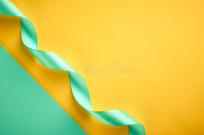 Green ribbon on green and yellow background composition, flat lay. And top view photo decoration celebration holiday design christmas gift card decorative bow stock photography