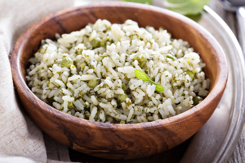 Green rice with herbs. In wooden bowl stock images