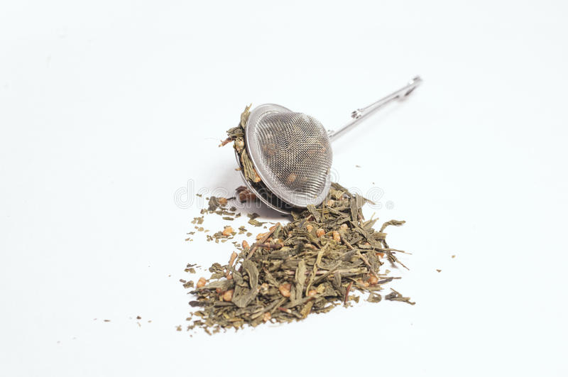 Green rice Tea Falling out of a Tea Strainer royalty free stock image