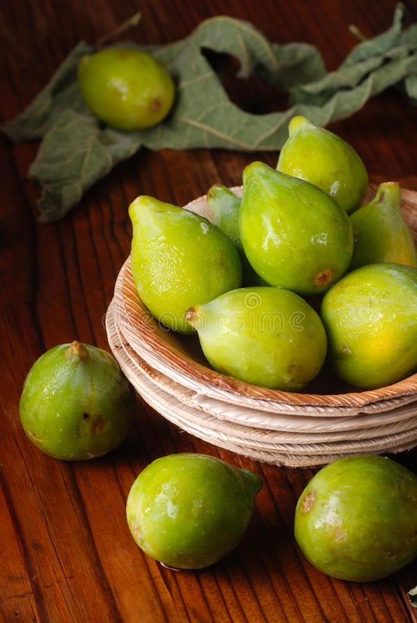 Green ripe figs. Ripe green figs on the wooden table stock photo
