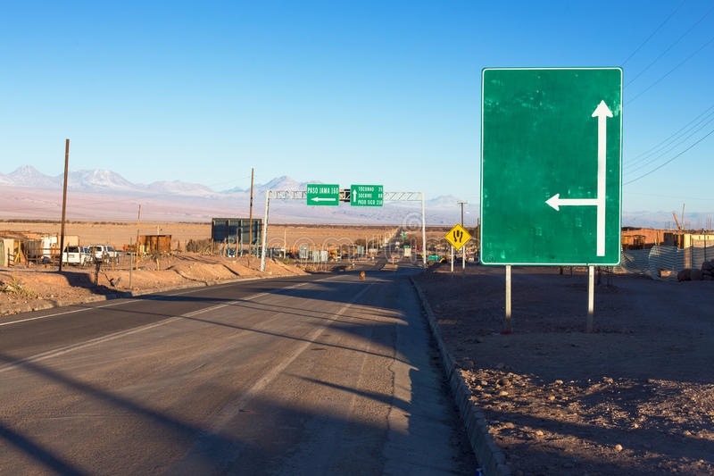 A green road sign stands next to a road in the atacama desert with an arrow going up and one to the right royalty free stock photo