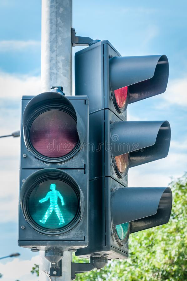 Green road traffic light signal for pedestrians on the crosswalk in the city royalty free stock photography
