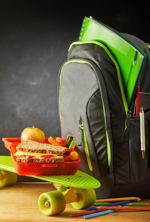 Green roller skate with school bag and lunch. Colorful green roller skate with school bag and open red plastic lunch box with a wholegrain cheese sandwich stock image