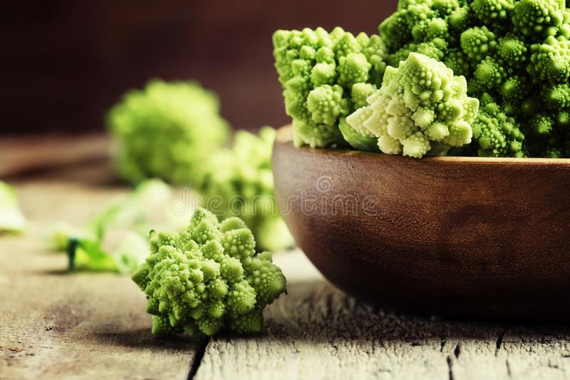 Green romanesco cauliflower in a wooden bowl, vintage wooden bac royalty free stock images