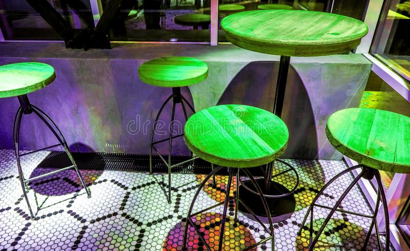 Green round chairs around high table at night cafe. Round table and three round chairs stand in empty cafe interior with black white mosaic floor at night side royalty free stock image