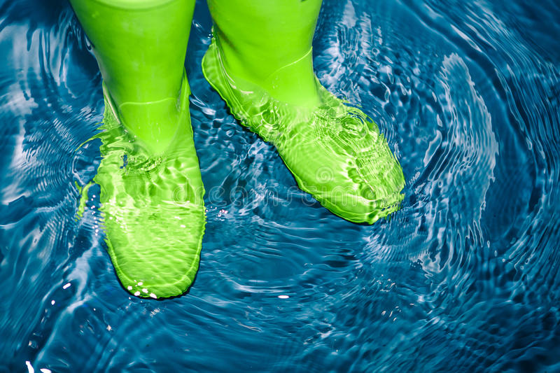 Green rubber boots in the water stock image