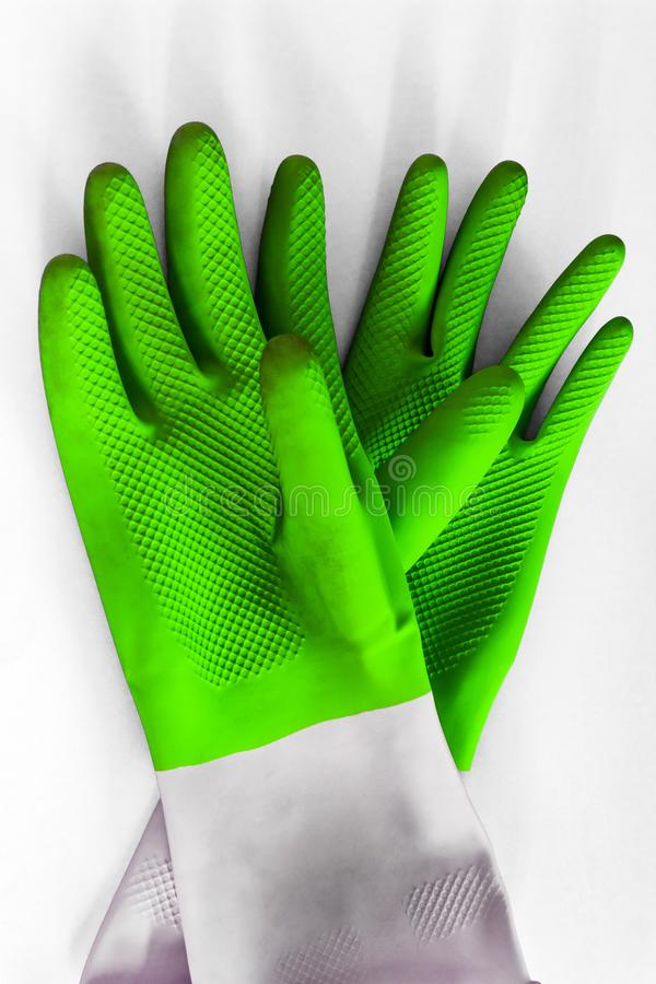 Green rubber protective gloves on the white background. Early spring or regular cleanup royalty free stock photo