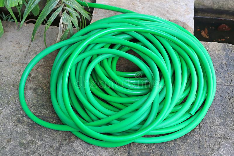 Green rubber tube for watering plants in the garden royalty free stock photography