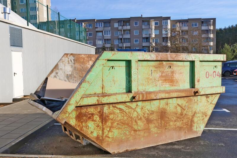 Green  rusty aged steel container for construction and industrial waste installed in a old  residential area. Of the European city stock photo