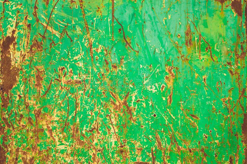 Green rusty and grungy metal iron plate wall with ferric oxide rust red color and with green peeling coating paint and scratches stock image