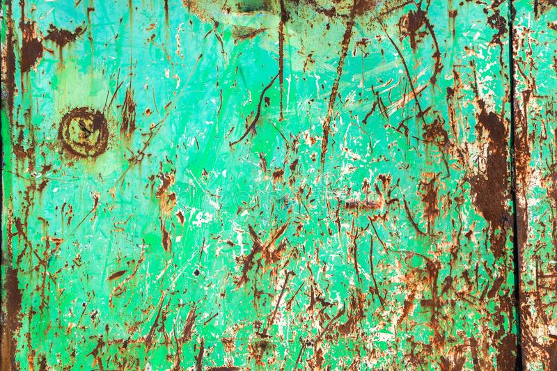 Green rusty and grungy metal iron plate wall with the typical ferric oxide red color and with green peeling coating paint royalty free stock photography