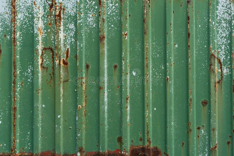 Green rusty metal fence. Corrugated metal sheet. Wall of green freight container. Vintage creative background stock photos