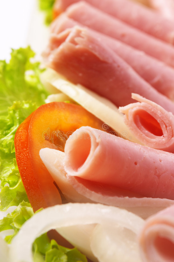Green salad. With onions, tomato, lettuce, and ham royalty free stock photo