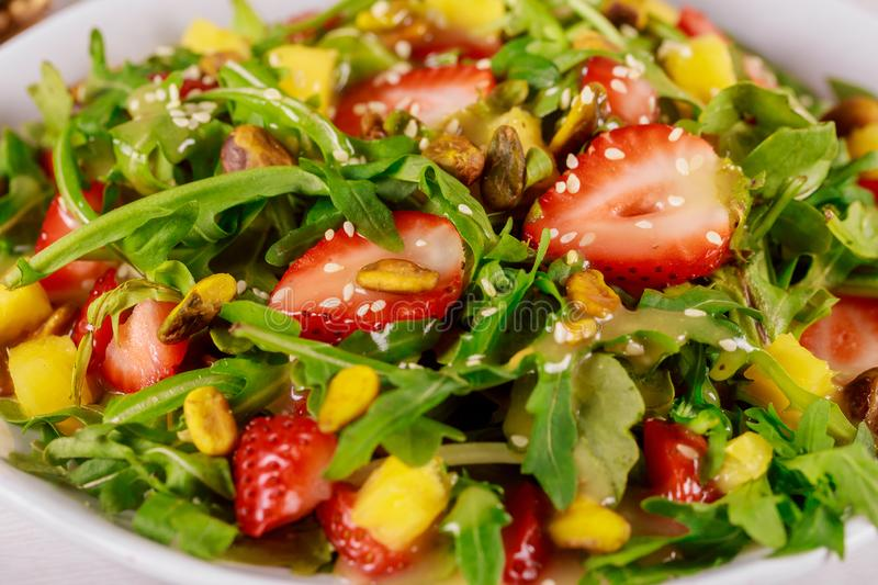 Green salad with arugula, strawberries, mango and pistachios. Close up, food, healthy, fresh, sesame, seeds, strawberry, lunch, plate, vegetable, delicious royalty free stock photos