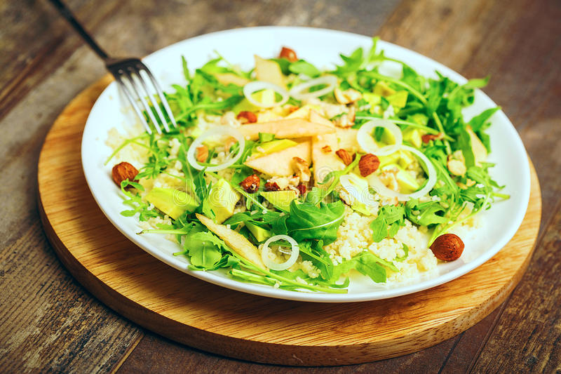 Green salad with avocado rucola nuts and couscous vegetarian healthy food. Close up view royalty free stock photography