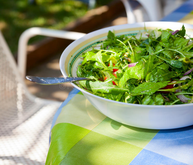 Green salad. Bowl of fresh italian green salad on a table outdoor royalty free stock image