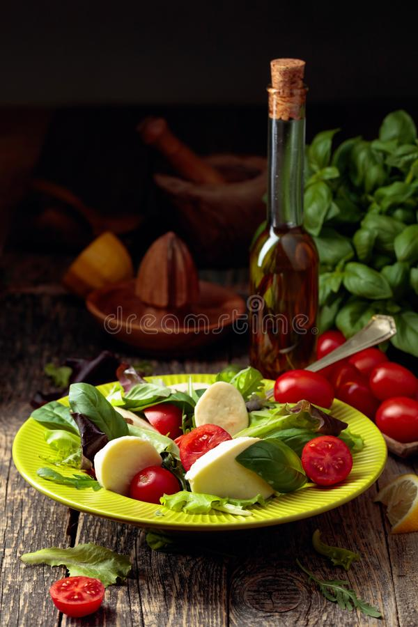 Green salad with mozzarella, tomato and basil in green plate on a old wooden background stock image