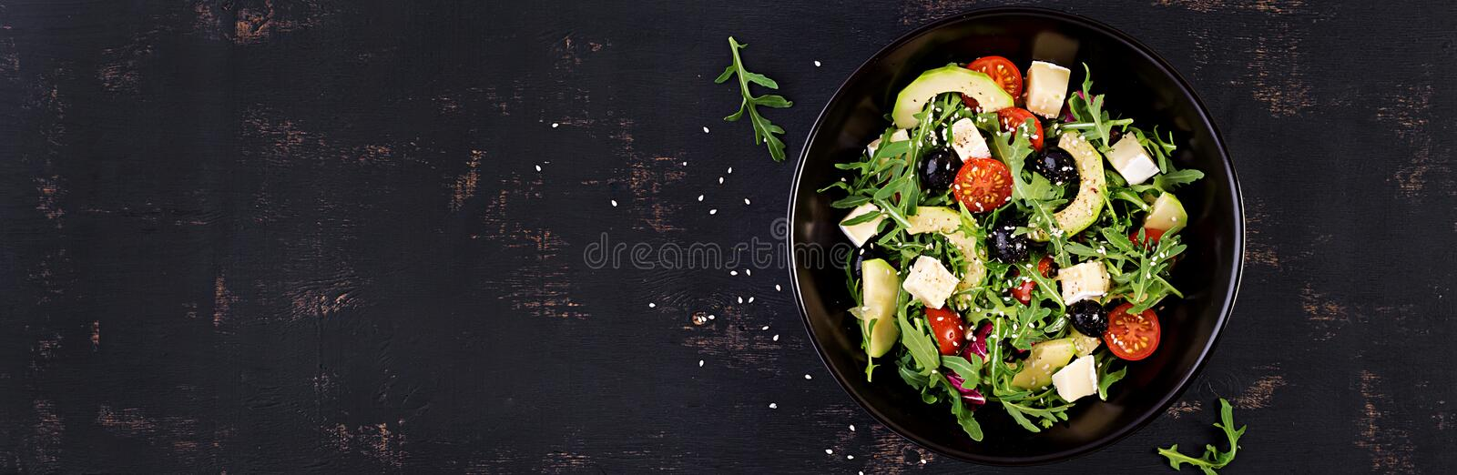 Green salad with sliced avocado, cherry tomatoes, black olives and cheese. Healthy diet vegetarian summer vegetable salad. Table setting. Food concept. Banner stock photos