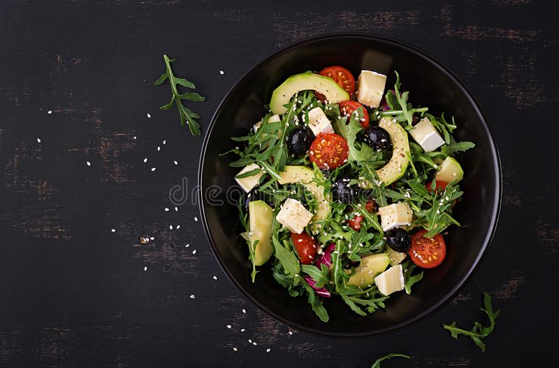 Green salad with sliced avocado, cherry tomatoes, black olives and cheese. Healthy diet vegetarian summer vegetable salad. Table setting. Food concept. Top royalty free stock photo