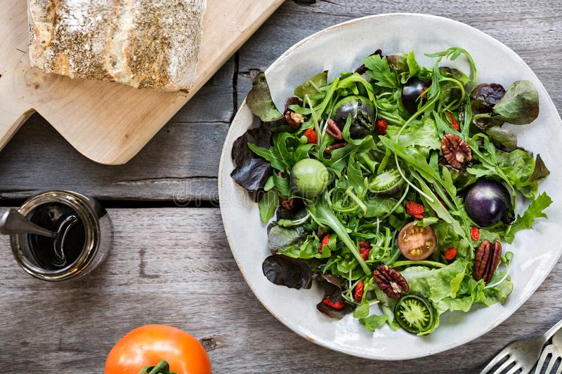 Green Salad with Green Tomatoes,Pecan and Goji berry. By Balsamic dressing and French bread stock photography