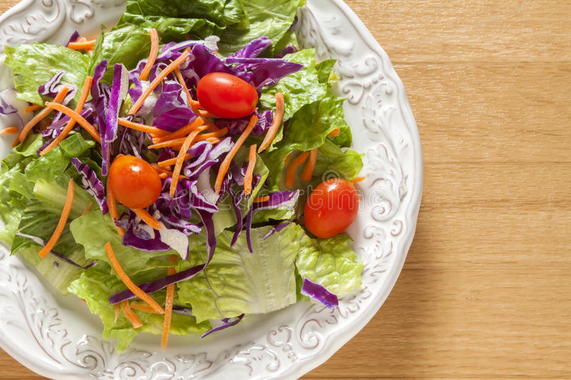 Green Salad in a white bowel. Green salad with tomato cabbage and carrots in a white bowel stock image