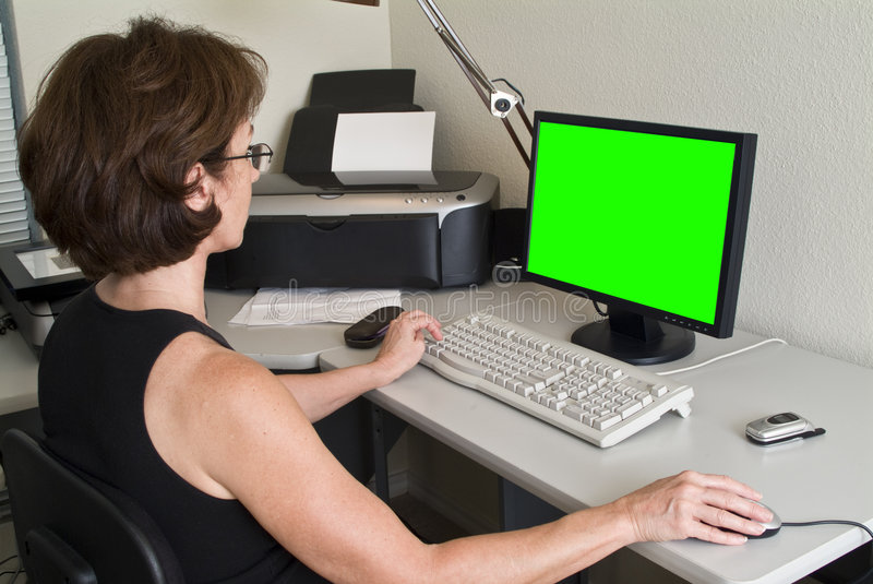 Green Screen Monitor. A woman siting at a desk working on her PC with green screen on the flat screen monitor stock photography