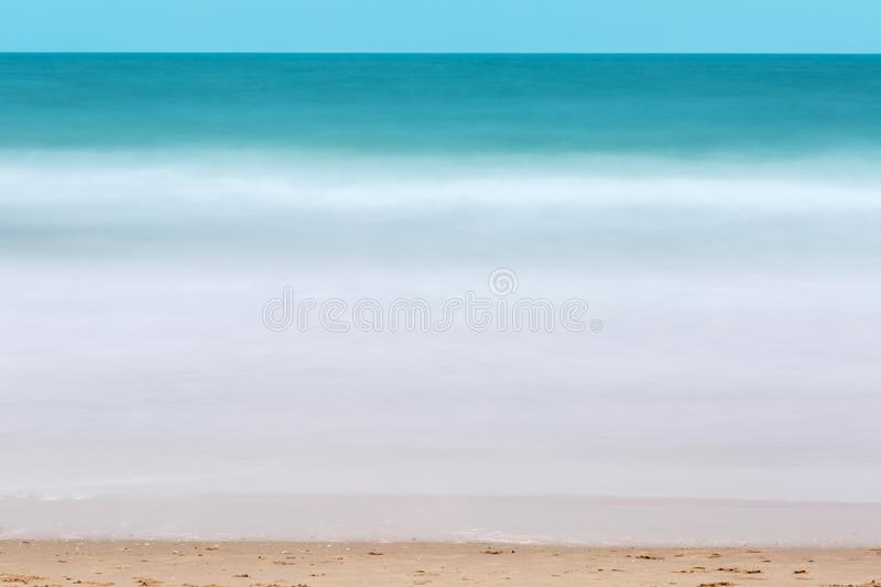 Green sea water flow surface and fluffy white breaking wave taken with long exposure on the beach for background. Motion blurred royalty free stock image