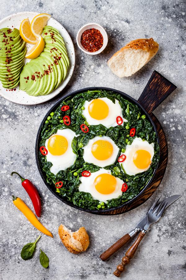 Green shakshuka with spinach, kale and peas. Healthy delicious breakfast with eggs, citrus salad, avocado. Top view, overhead. Green shakshuka with spinach, kale royalty free stock images
