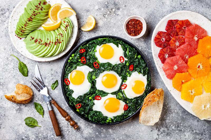 Green shakshuka with spinach, kale and peas. Healthy delicious breakfast with eggs, citrus salad, avocado. Top view, overhead, flat lay stock images