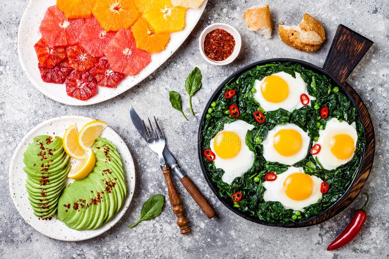 Green shakshuka with spinach, kale and peas. Healthy delicious breakfast with eggs, citrus salad, avocado. Top view, overhead. Flat lay stock images
