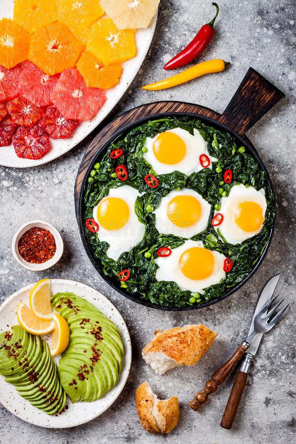Green shakshuka with spinach, kale and peas. Healthy delicious breakfast with eggs, citrus salad, avocado. Top view, overhead. Flat lay royalty free stock photo