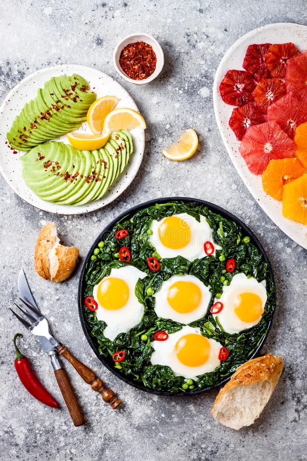 Green shakshuka with spinach, kale and peas. Healthy delicious breakfast with eggs, citrus salad, avocado. Top view, overhead. Flat lay royalty free stock photography