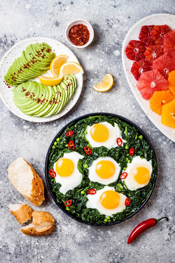 Green shakshuka with spinach, kale and peas. Healthy delicious breakfast with eggs, citrus salad, avocado. Top view, overhead stock photography
