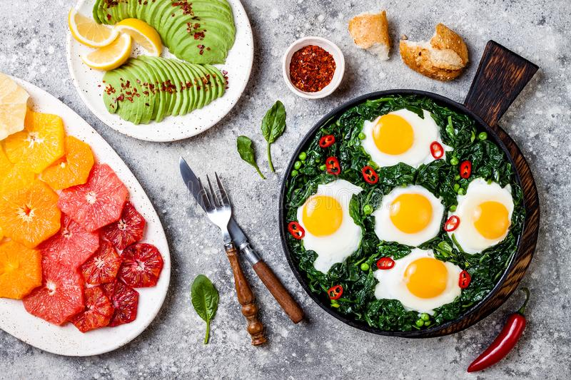Green shakshuka with spinach, kale and peas. Healthy delicious breakfast with eggs, citrus salad, avocado. Top view, overhead. Flat lay stock photo