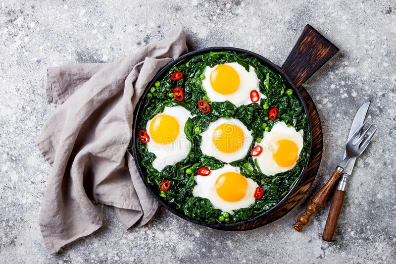 Green shakshuka with spinach, kale and peas. Healthy delicious breakfast. Top view, overhead, flat lay. Green shakshuka with spinach, kale and peas. Healthy royalty free stock photo