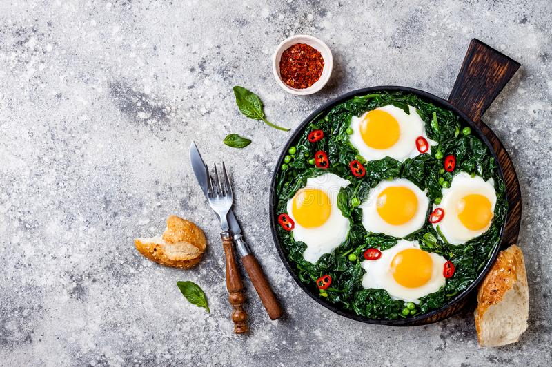 Green shakshuka with spinach, kale and peas. Healthy delicious breakfast. Top view, overhead, flat lay. Green shakshuka with spinach, kale and peas. Healthy stock photo