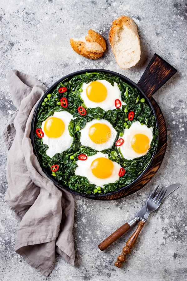 Green shakshuka with spinach, kale and peas. Healthy delicious breakfast. Top view, overhead, flat lay. Green shakshuka with spinach, kale and peas. Healthy stock image