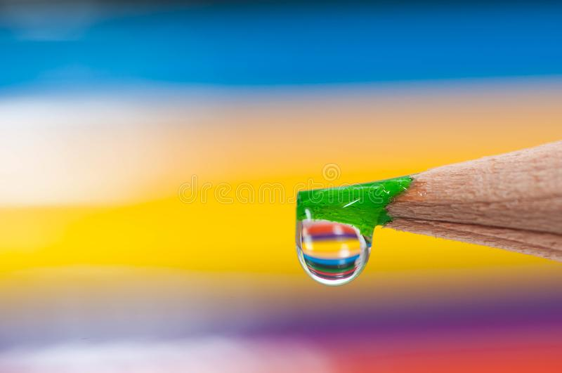 Green sharp color pencil on focus, waterdrop on it. Reflecting the background pencils royalty free stock images