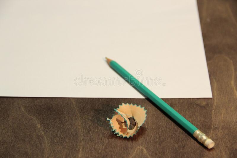 Green sharpened pencil and a blank sheet of paper. Beginning of work and creativity. royalty free stock image