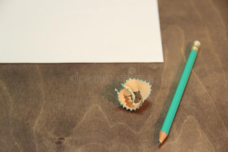 Green sharpened pencil and a blank sheet of paper. Beginning of work and creativity. stock image