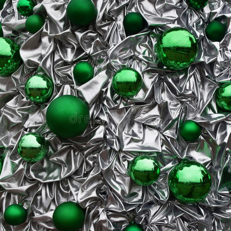 Green shiny xmas balls on crumpled background. Green round glass shiny different size xmas balls on grey silver color crumpled metallic background as decorative stock photo