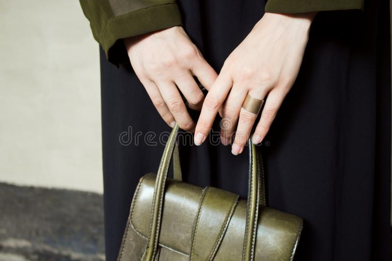 Green shirt and black dress, with green leather handbag, on gray concrete background. stock images