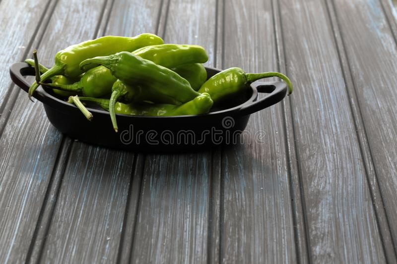 Green Shishito peppers in a metal container on wooden background stock images