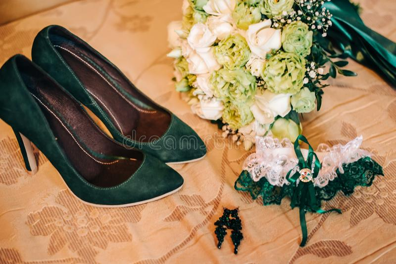 Green shoes with a green garter for the bride stock photography