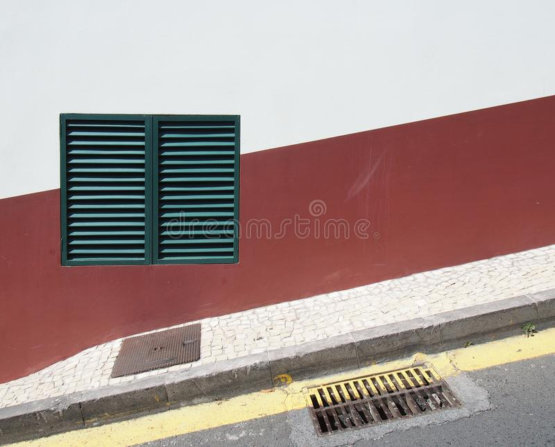 A green shuttered closed window on a red and white house wall on a sloping street with yellow parking line and pavement in typical. Portuguese colours royalty free stock image