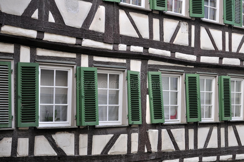 Green shutters on wattle facade, tubingen. Detail of misaligned windows on old wattle building in city center royalty free stock photography