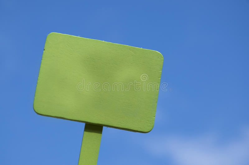 Green Sign on Bright Blue Cloudy Sky stock photography